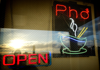 Vietnamese pho neon sign in window with sky and sun reflection